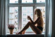 Ню блондинка молода жінка з чашкою кави, сидячи на підвіконні ранок — стокове фото