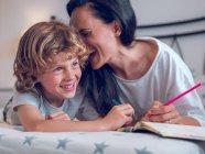 Hermosa mujer y lindo niño acostado en la cama cómoda y para colorear imágenes en cuaderno juntos - foto de stock