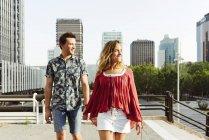 Пара тримається за руки і ходить по вулиці. — стокове фото