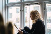 Femme rêveuse lisant un livre assis sur le rebord de la fenêtre à la maison — Photo de stock
