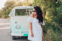 Cheerful brunette woman in summer dress and sunglasses posing near van in nature — Stock Photo