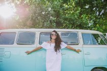 Cheerful brunette woman in sunglasses posing near van — Stock Photo