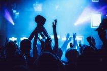Анонімні люди тримають руки і підбадьорюючи, проводячи час на дивовижне шоу музики — стокове фото