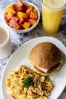 Hamburger and omelette on plate served with fruits and juice — Stock Photo