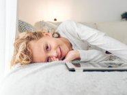 Mignon garçon souriant, couché sur le canapé avec tablette numérique — Photo de stock