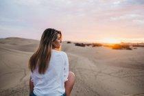 Молодая женщина в белой футболке сидит на песке на закате и смотрит через плечо — стоковое фото
