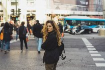 Giovane donna con zaino guardando indietro mentre cammina sulla strada della città — Foto stock