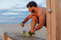 Мускулистый бородатый мужчина проверяет современный фитнес-трекер во время тренировки на пляже — стоковое фото