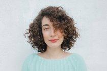 Приваблива молода брюнетка з кучерявим волоссям дивиться на камеру, стоячи біля білої стіни. — стокове фото