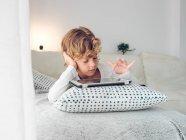 Garçon à l'aide de tablette numérique en position couchée sur le canapé à la maison — Photo de stock