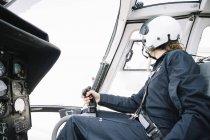 Donna pilota nel casco che si siede in elicottero e di funzionamento — Foto stock