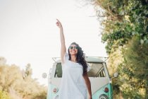 Cheerful brunette woman posing in front of van in nature — Stock Photo