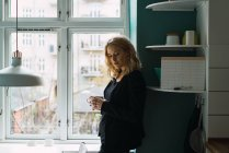 Romantic blonde woman standing with cup at window at home — Stock Photo