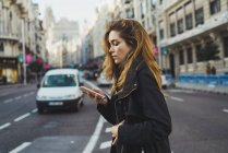 Woman using smartphone on road in city — Stock Photo