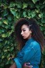 Selbstbewusste Afroamerikanerin steht vor grünem Laub — Stockfoto