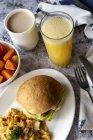Hamburger e frittata sul piatto servito con frutta e succhi di frutta — Foto stock