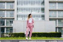 Стильная молодая женщина в розовом стоит перед современным офисным зданием — стоковое фото