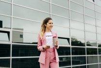 Веселая модная женщина в розовом костюме с кофе, стоящая перед современным офисным зданием — стоковое фото