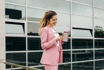 Веселая женщина в розовом костюме с кофе с помощью смартфона перед современным офисным зданием — стоковое фото