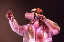 Young woman touching air and wearing virtual reality headset in pink neon light — Stock Photo