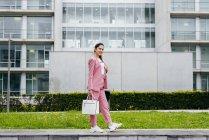 Стильная женщина в розовом костюме стоит перед современным офисным зданием — стоковое фото