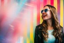 Портрет щасливі молоду жінку в сонцезахисні окуляри барвисті тлі — стокове фото