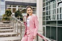 Усміхаючись модний жінка з кави, стоячи на кроки і спершись на перила металеві — стокове фото
