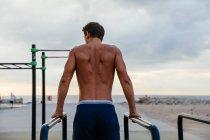 Un atleta masculino hace ejercicio en un gimnasio exterior - foto de stock