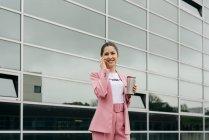 Веселая стильная женщина с кофе разговаривает на смартфоне перед современным офисным зданием — стоковое фото