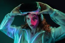 Young woman wearing VR glasses in neon light on black background — Stock Photo