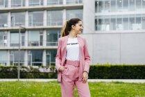 Улыбающаяся модная женщина в розовом костюме стоит перед современным офисным зданием — стоковое фото