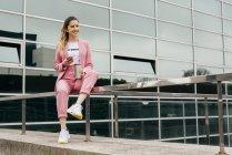 Модная молодая женщина в розовом костюме с кофе и телефоном сидит на перилах перед современным офисным зданием — стоковое фото