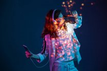 Woman dancing with smartphone and headphones in neon light — Stock Photo
