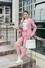 Mulher na moda com café de pé em passos e inclinando-se sobre trilhos de metal — Fotografia de Stock