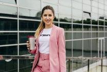 Модная молодая женщина с кофе стоит перед современным офисным зданием — стоковое фото