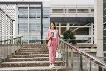 Jeune femme élégante portant un costume rose avec des baskets blanches marchant en bas avec une tasse de café devant un immeuble de bureaux — Photo de stock