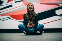 Jovem feliz sentada no chão com telefone celular e ouvindo música contra fundo colorido — Fotografia de Stock
