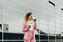 Модная женщина пьет кофе, стоя перед современным офисным зданием — стоковое фото