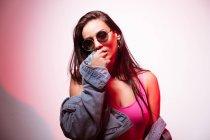 Красивая молодая розовая женщина в солнечных очках стоит у белой стены и смотрит в камеру — стоковое фото