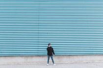 Jeune adolescent debout au mur de métal et parlant sur téléphone mobile — Photo de stock