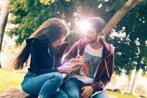 Сміючись молода пара сидить з смартфон в парку — стокове фото
