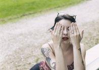 Молодая хипстерша сидит на улице и закрывает лицо руками — стоковое фото