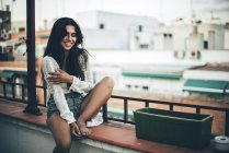 Young happy woman sitting at balcony and smiling on background of houses — Stock Photo