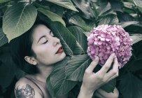 Чувственная молодая женщина трогает розовый цветок, растущий на кусте — стоковое фото