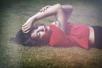 Чувственная хипстерша в красной футболке, лежащая на траве — стоковое фото
