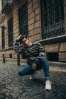 Молодий стильний підліток у светр crouching на вулиці міста і, дивлячись на камеру — стокове фото