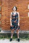 Татуированная женщина в узорчатом платье, стоящая перед кирпичной стеной — стоковое фото