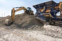 Terra cava con pesanti macchinari industriali sul cantiere — Foto stock