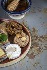 Dolci tipici marocchini con miele e mandorle su piatto di legno sulla superficie grigio squallido — Foto stock