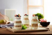 Frascos de vidro com granola e iogurte em placa de madeira — Fotografia de Stock